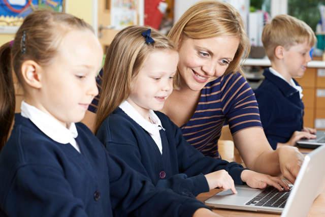 Teacher Helping Female Elementary School Pupils In Computer Class